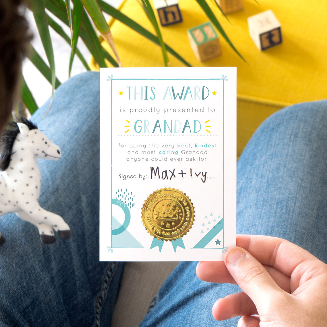 A Grandad certificate award card printed onto white card in varying tones of blue and pops of yellow! Each card features a shiny gold seal to make it official! Photographed over a lap with a yellow footrest in the background.