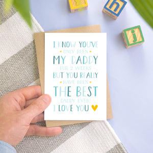 A personalised new daddy card photographed on a blue and grey stripy background with a few leaves, and wooden building blocks. The card is being held by a father and features typography in varying tones of blue and with a pop of yellow.
