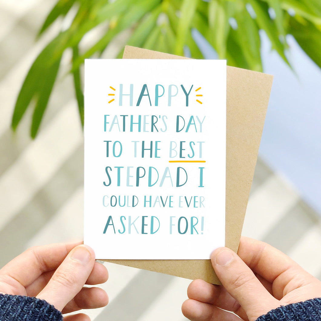 Happy Father's Day to the best stepdad I could have ever asked for Father's Day card. It has been photographed over a grey striped rug with a blue floor and some leafy foliage. It is also being held by a man.