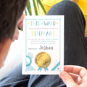 A stepdad award certificate card printed onto white card, with varying tones of blue and pops of yellow. This card is photographed being held over black jeans and a yellow footrest.