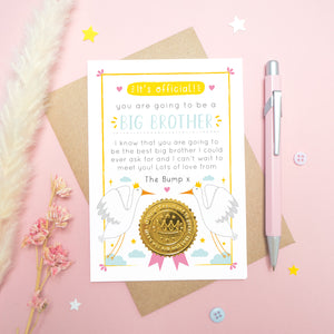 A big brother announcement card from the bump photographed on a pink background with dried flowers, a pen, buttons and stars.