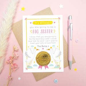 A big sister announcement card from the bump photographed on a pink background with dried flowers, a pen, buttons and stars.