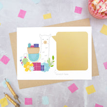 Load image into Gallery viewer, A personalised Llama birthday scratch card shot on a grey background with scattered confetti, a birthday cupcake and candles. This image is an example of how to card looks once the message has been covered with the gold scratch off panel. The card features a llama carrying gifts.