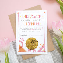 Load image into Gallery viewer, A mother's day certificate for Stepmum showing the card before a child has written on the front. This is how your card will arrive. It has been shot over head on a kraft brown envelope with a pink and white and grey background with tulips.