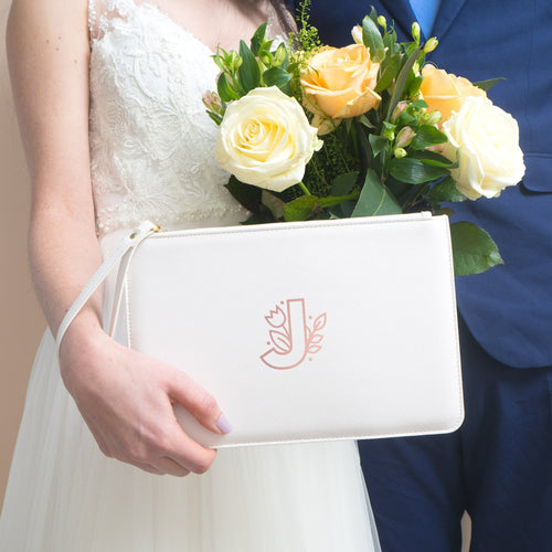 A wedding wristlet pouch with a floral monogram letter J. The pouch is white and the initial is in rose gold.