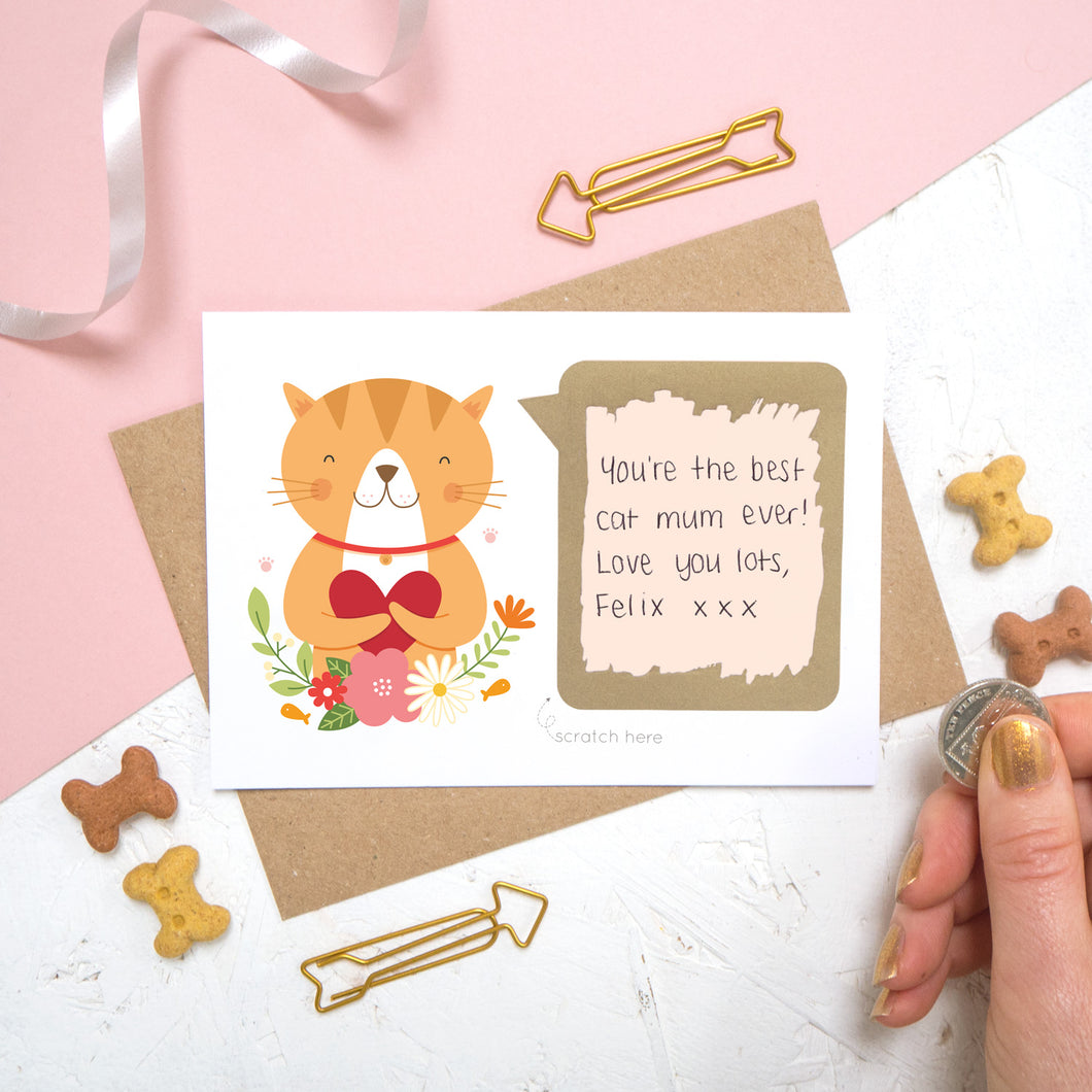 A personalised cat scratch card with the hand written message revealed after it has been scratched off. The card is shot on a pink and white background with animal biscuits.