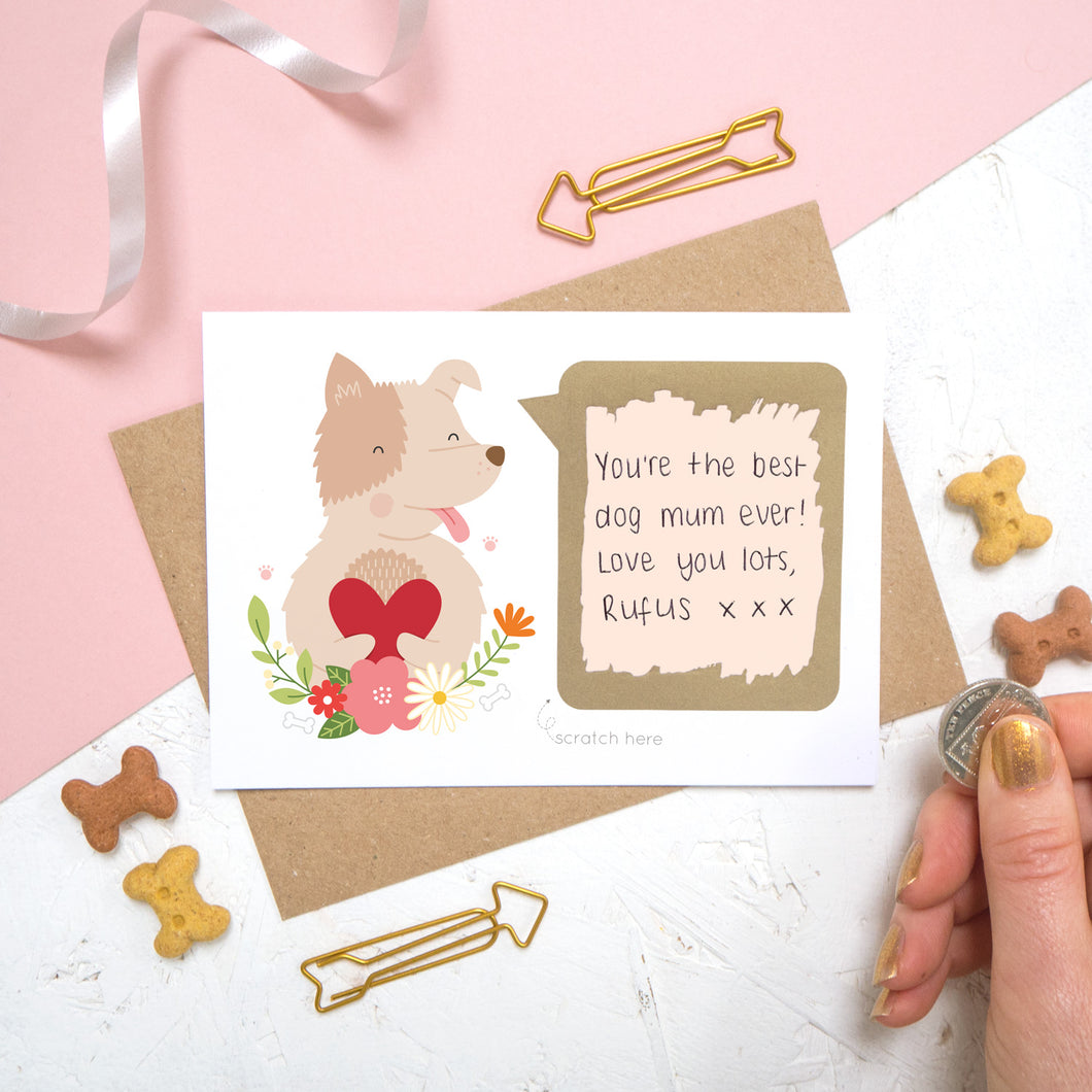 A personalised dog scratch card with a hand written message that has been scratched off. Photographed on a pink and white background with dog biscuits for props.