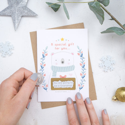 A Christmas baby announcement scratch card that has just been scratched off where the message reads 'you are going to be a grandma'. The card is on a white background surrounded with baubles, foliage and hands.