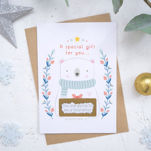 A Christmas baby announcement scratch card that has just been scratched off where the message reads 'you are going to be a grandma'. The card is on a white background surrounded with baubles, foliage and snow flakes