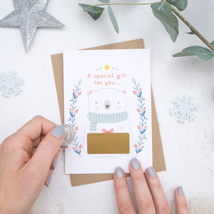 A Christmas baby announcement scratch card with a gold panel that is about to be scratched off. The card is on a white background surrounded with baubles, foliage and hands.