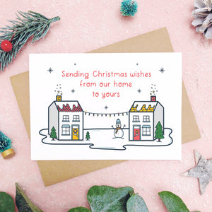 A sending wishes from our home to yours card photographed on a pink background with grey and green foliage. The card features two little houses connected by fairy lights.