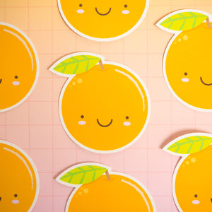 Satsuma orange stickers arranged on a pink squared background.