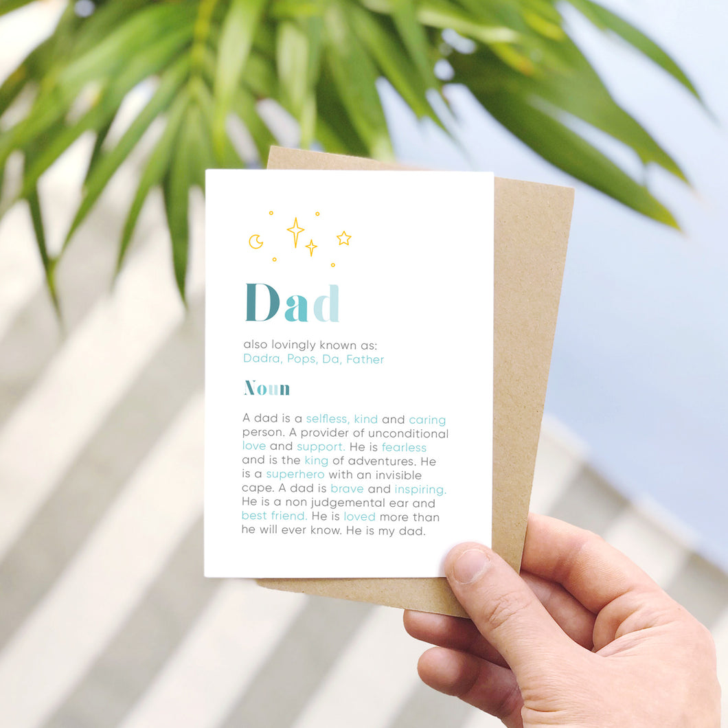 A personalised Dad dictionary definition card, shot on a grey stripy and blue background. The card features a definition of a dad in grey and blue text with yellow stars and dots.