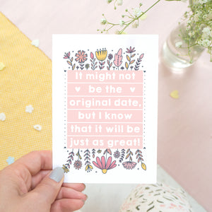 Original wedding date card for wedding postponements or delays. Photographed being held over a white, yellow and pink textured background with a pink pen and hint of foliage. The card features pink block of text and hand drawn florals.