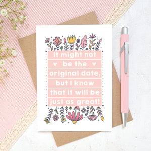 Original wedding date card for wedding postponements or delays. Photographed on a white and pink textured background with a pink pen and hint of foliage. The card features pink block of text and hand drawn florals.