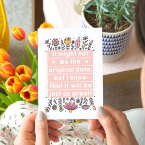 Original wedding date card for wedding postponements or delays. Photographed in a lifestyle setting with tulips, a person and plants on a table.. The card features pink block of text and hand drawn florals.