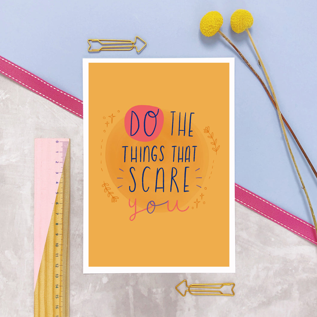Do the things that scare you A5 print in yellow and photographed on a lilac background with a ruler and yellow flowers