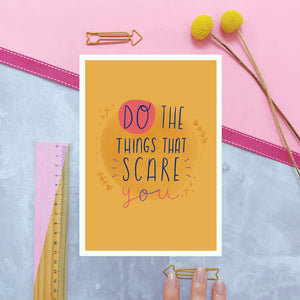 Do the things that scare you A5 print in yellow and photographed on a pink background with a ruler and yellow flowers