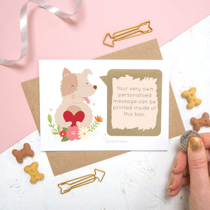 A personalised dog scratch card with a printed message that has been scratched off. Photographed on a pink and white background with dog biscuits for props.