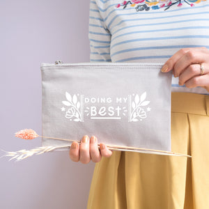 Doing my best cotton accessory pouch in grey with the white text and florals. Photographed on a lilac background. Model holds the pouch with dried grass, wearing a stripy top and yellow skirt.