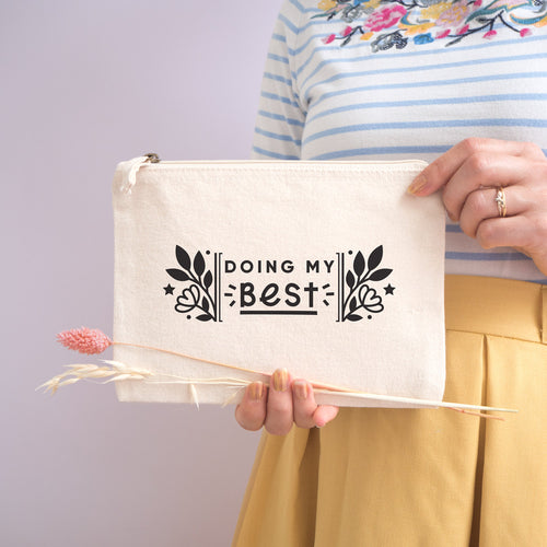 Doing my best cotton accessory pouch in natural with the black text and florals. Photographed on a lilac background. Model holds the pouch with dried grass, wearing a stripy top and yellow skirt.