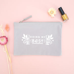 Doing my best cotton accessory pouch in grey with the white text and florals. Photographed on a pink background with dried flowers and gold nail varnish.