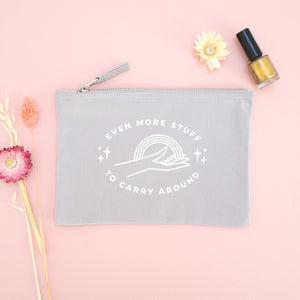 Even more stuff to carry around zipped cotton pouch in grey with white text. Photographed on a pink background with dried flowers and gold nail varnish.