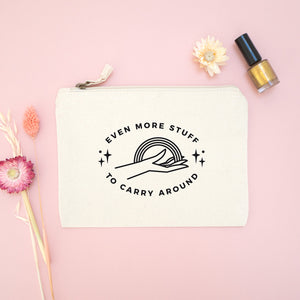 Even more stuff to carry around zipped cotton pouch in natural with black text. Photographed on a pink background with dried flowers and gold nail varnish.