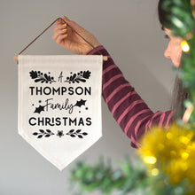 Load image into Gallery viewer, A personalised family Christmas banner flag personalised with your family name and adorned with festive flourishes! Each flag has a black print on natural coloured linen.