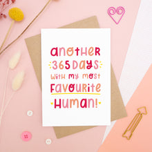 Load image into Gallery viewer, The 'another 365 days with my most favourite human' card photographed on a pink background with dried flowers, buttons and paper clips as props.