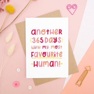 The 'another 365 days with my most favourite human' card photographed on a pink background with dried flowers, buttons and paper clips as props.