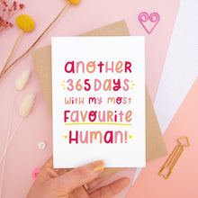 Load image into Gallery viewer, The 'another 365 days with my most favourite human' card photographed on a pink background with dried flowers, buttons and paper clips as props. The card itself is being held above the scene.