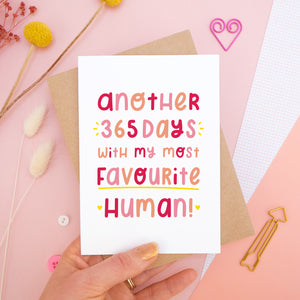 The 'another 365 days with my most favourite human' card photographed on a pink background with dried flowers, buttons and paper clips as props. The card itself is being held above the scene.