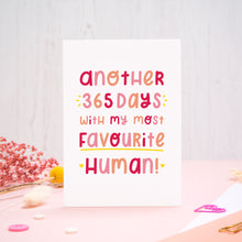 Load image into Gallery viewer, The 'another 365 days with my most favourite human' card photographed standing up against an off white background with flowers, buttons and paperclips at the base of the card.