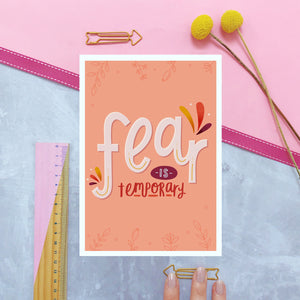 Fear is temporary empowerment print in shades of peach and red, photographed on a marble and pink background.