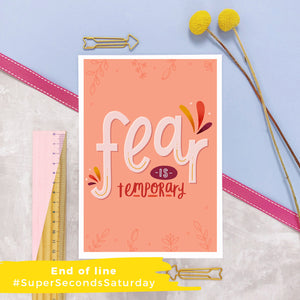 Fear is temporary empowerment print in shades of peach and red, photographed on a marble and lilac background.