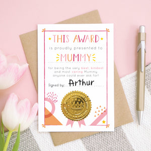 A Mummy certificate card for mother's day featuring a shiny gold seal. This card is pink and peach in colour with a small pop of yellow and has been shot over head on a pink and grey and white background. There is a gold pen for scale and tulips on the left.