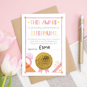 A stepmum certificate card for mother's day featuring a shiny gold seal. This card is pink and peach in colour with a small pop of yellow and has been shot over head on a pink and grey and white background. There is a gold pen for scale and tulips on the left.