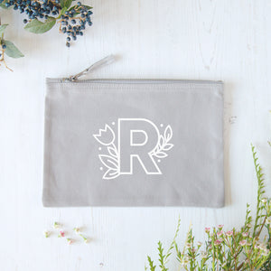 A grey cotton zipped pouch with a floral initial R printed in white.