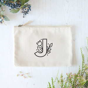 A natural cotton zipped pouch with a floral initial J printed in black.