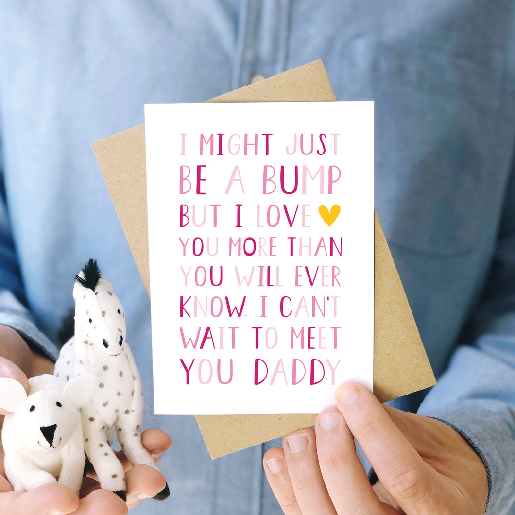 I can't wait to meet you card from the bump to daddy fathers day card photographed being held by a man in a blue button up shirt and with two cuddly toys. This design is shown in varying tones of pink and a pop of yellow.