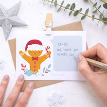 Load image into Gallery viewer, A personalised gingerbread man scratch card with the handwriting element being demonstrated. Shot on a white background with a glittery star and sprig of eucalyptus.