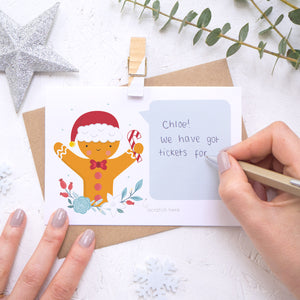 A personalised gingerbread man scratch card with the handwriting element being demonstrated. Shot on a white background with a glittery star and sprig of eucalyptus.