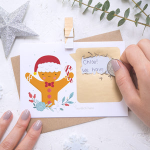 A personalised gingerbread man scratch card where the scratching off of the gold panel is being demonstrated. Shot on a white background with a glittery star and sprig of eucalyptus.