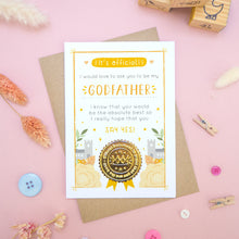 Load image into Gallery viewer, A will you be my godfather card in orange, shot on a pink background surrounded by dry flowers, buttons and building blocks.