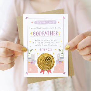 A will you be my godfather card in purple and pink being held by both hands in front of a person wearing a pink cardigan and a white dress.