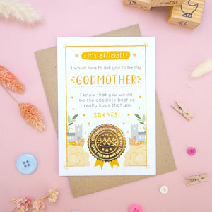 A will you be my godmother card in orange, shot on a pink background surrounded by dry flowers, buttons and building blocks.
