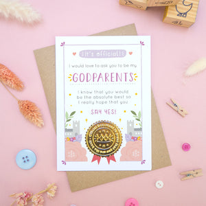 A will you be my godparents card in pink and purple, shot on a pink background surrounded by dry flowers, buttons and building blocks.