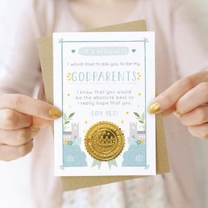 A will you be my godparents card in blue being held by both hands in front of a person wearing a pink cardigan and a white dress.