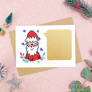 A make your own scratch card with a childs drawing of santa and an example of the panel after it has been applied. Shot on pink with snow and greenery.